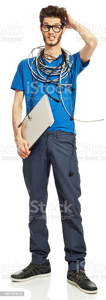 Geek Portrait of distraught young man with a lot of cables on his neck, holding a laptop in hand. Studio shot, white background. 18-19 Years Stock Photo