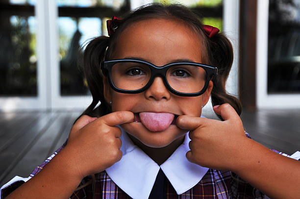 Geeky school girl poking her tongue out stock photo