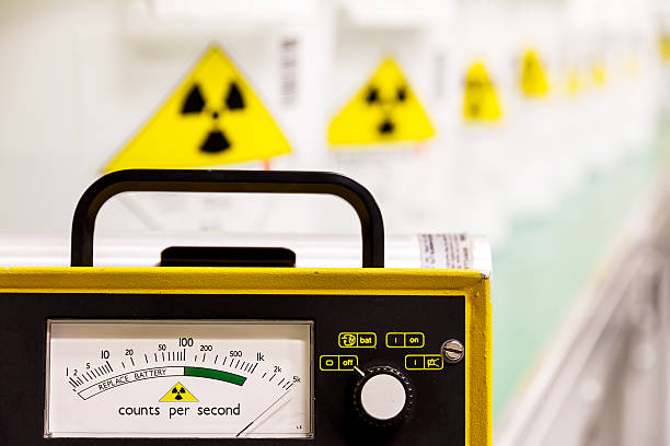 Geiger counter with yellow hazard signs in row fading behind Geiger counter with radioactive materials in the background radioactive contamination stock pictures, royalty-free photos & images