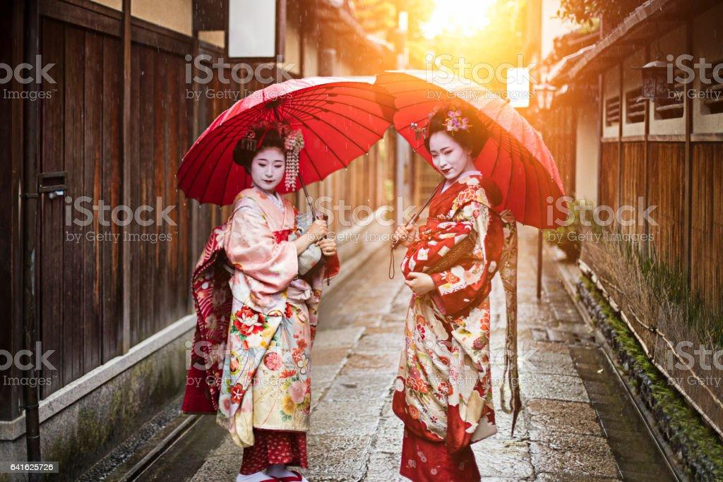 Geisha girls holding red umbrellas on footpath stock photo