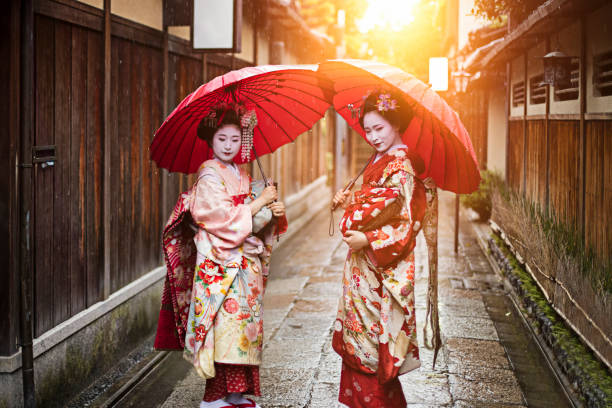 geisha girls holding red umbrellas on footpath - geisha girl stock photos and pictures