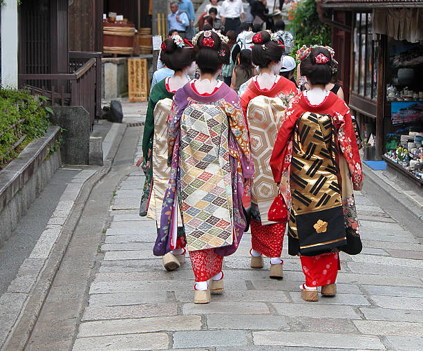 geisha group in a kyoto street - geisha girl stock photos and pictures