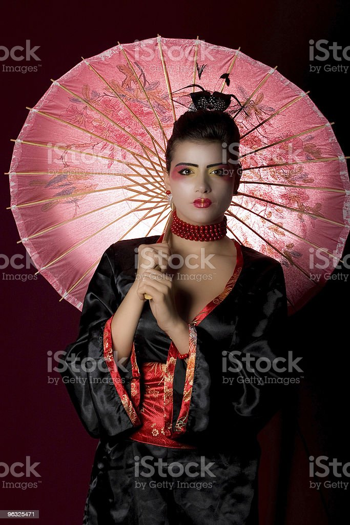 Geisha in studio with backlit painted umbrella royalty-free stock photo
