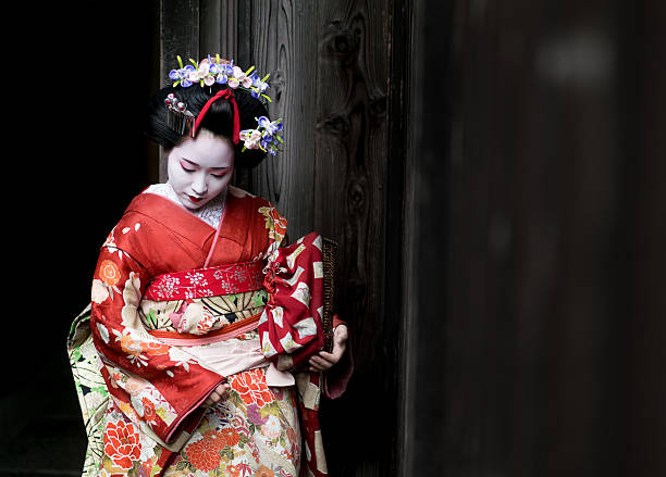 Geisha wearing a beautiful kimono Portrait of a Geisha wearing a beautiful kimono and traditional  clothing - Japanese culture geisha stock pictures, royalty-free photos & images