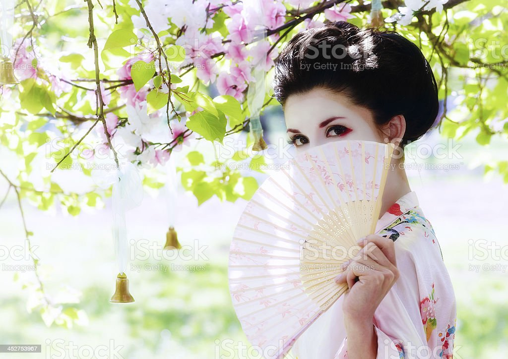 Geisha with fan in the garden stock photo
