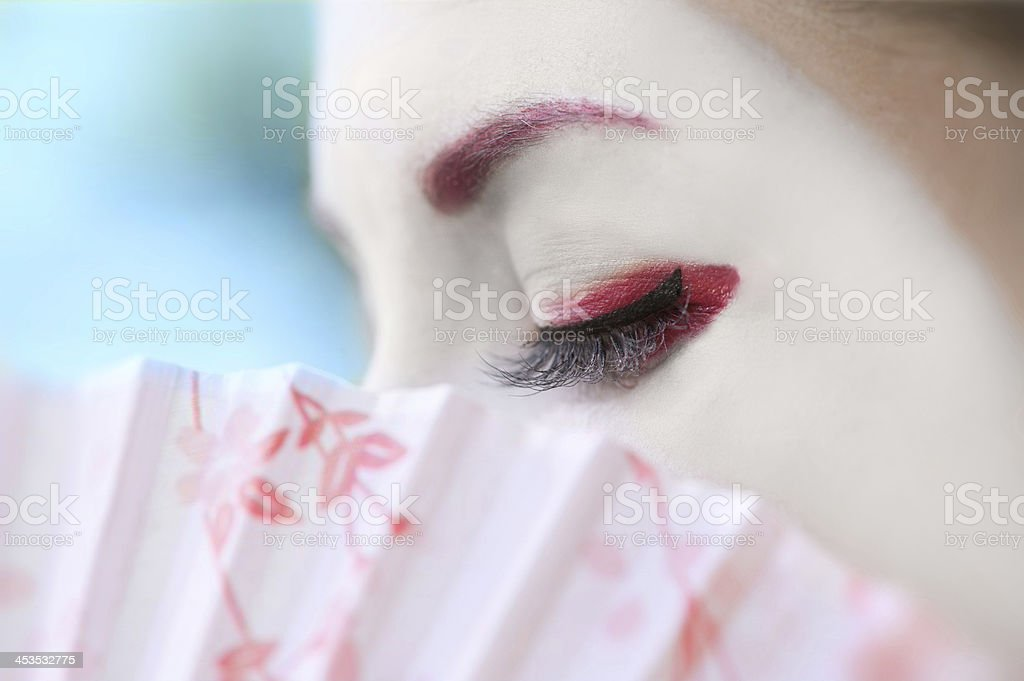 Geisha with fan (closeup, blue background) stock photo