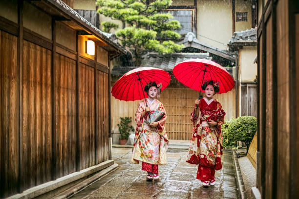 Geishas holding red umbrellas during rainy season Full length of young maikos holding red umbrellas during rainy season. Beautiful geisha girls wearing traditional dress called kimono. They are walking on wet street. geisha stock pictures, royalty-free photos & images