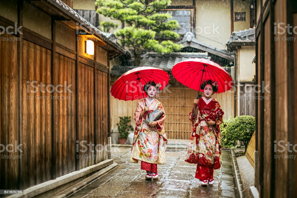 Geishas holding red umbrellas during rainy season stock photo