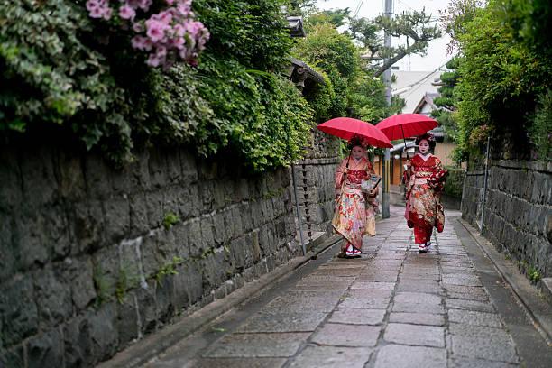 geishas walking outdoors holding umbrellas - natürliche make up kurse stock-fotos und bilder