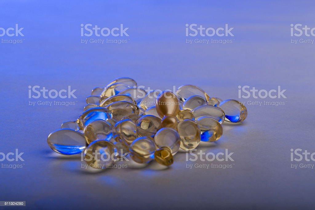 Gel capsules on the white background illuminated with blue lighting stock photo