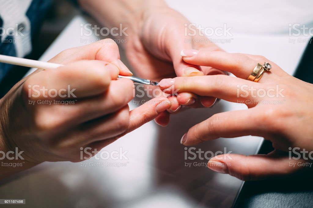 Gel nail extensions build up process. Women at beauty parlour doing manicure. stock photo
