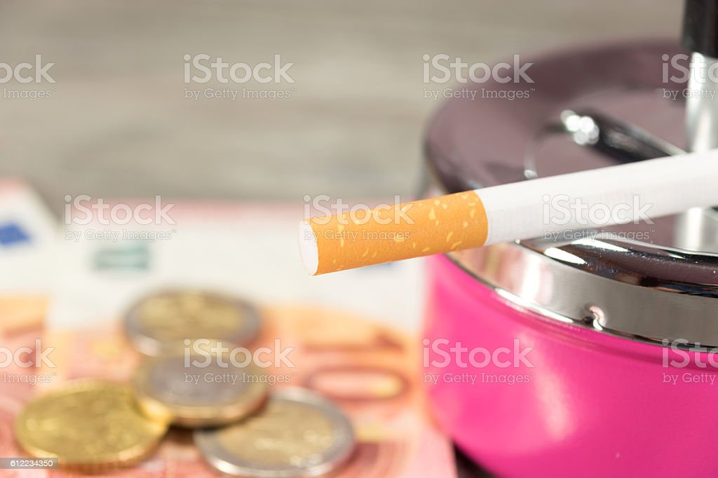Geld, Zigarette und ein Aschebecher stock photo