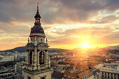 Aerial cityscape of Budapest with landmarks buildings including Gellert Hill with Citadella, Castle Hill and St Stephen's Basilica at sunset.