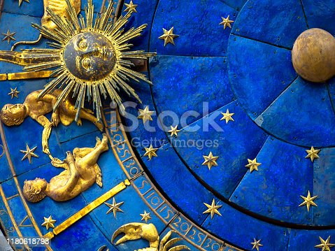 904302038 istock photo Gemini astrological sign on ancient clock. Detail of Zodiac wheel with Sun and Twins. 1180618798