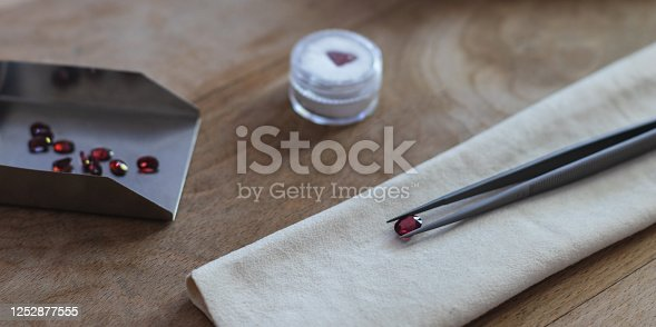 Gemology work table with tweezers, suede and shovel with ruby gemstones.