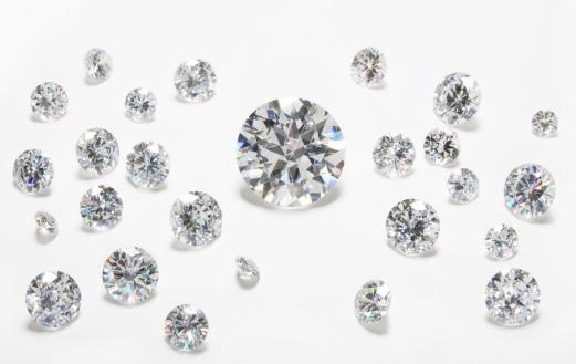 Colorless gem arrangement. Stones show fire. Focus on large center stone.