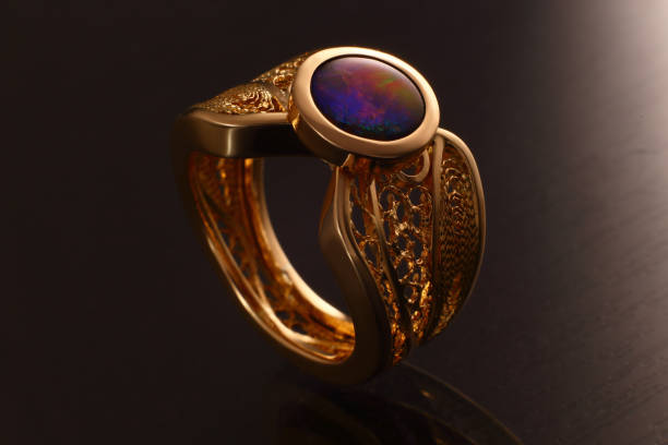 gemstone ring in gold , jewelry band with ammolite , diamond and emeralds - filigree stock photos and pictures