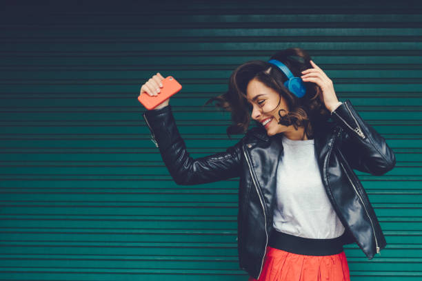 Gen Z girl enjoying disco music Beautiful woman dancing to the music against coloured wall music stock pictures, royalty-free photos & images
