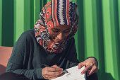 Gen Z Muslim woman sketching while outdoors