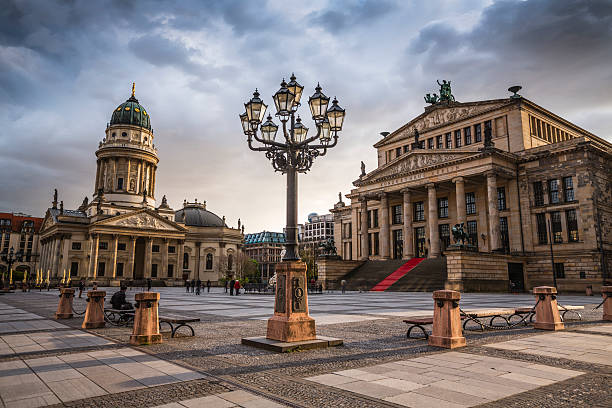 Gendarmenmarkt in Berlin, Germany Gendarmenmarkt square in Berlin with moody sunset clouds. View on German Cathedral and Konzerthaus gendarmenmarkt stock pictures, royalty-free photos & images
