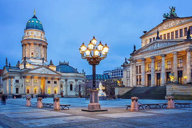 Gendarmenmarkt square in Berlin, Germany Panoramic view of famous Gendarmenmarkt square with illuminated Berlin Concert Hall and German Cathedral in twilight during blue hour at dusk, Berlin Mitte district, Germany gendarmenmarkt stock pictures, royalty-free photos & images