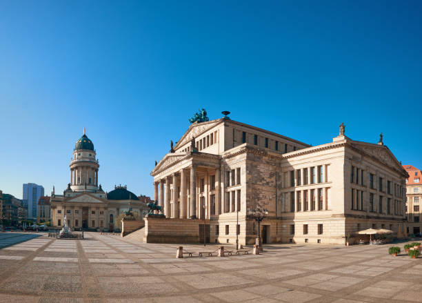 Gendarmenmarkt square in Berlin with German church and Concert Hall Gendarmenmarkt square in Berlin with German church and Concert Hall on a bright day, panoramic image gendarmenmarkt stock pictures, royalty-free photos & images