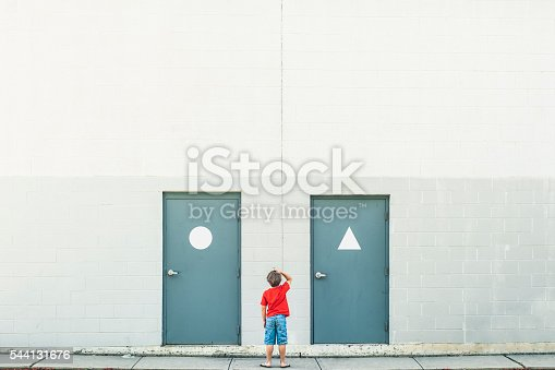 Small confused child scratching his head standing inbetween doors with gender signs, plenty of copyspace.