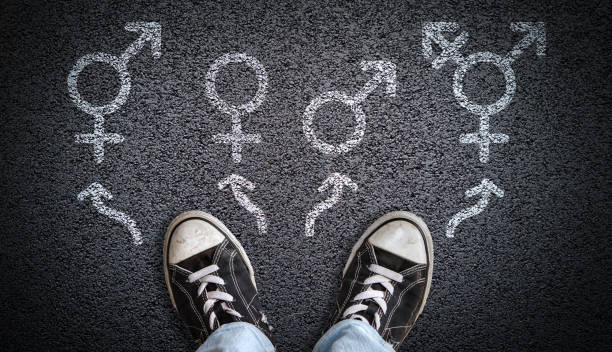 Gender Dysphoria, Confusion or Choice A person standing on asphalt road with gender symbols of male, female, bigender and transgender.  Concept of choice or gender confusion or dysphoria. transgender stock pictures, royalty-free photos & images