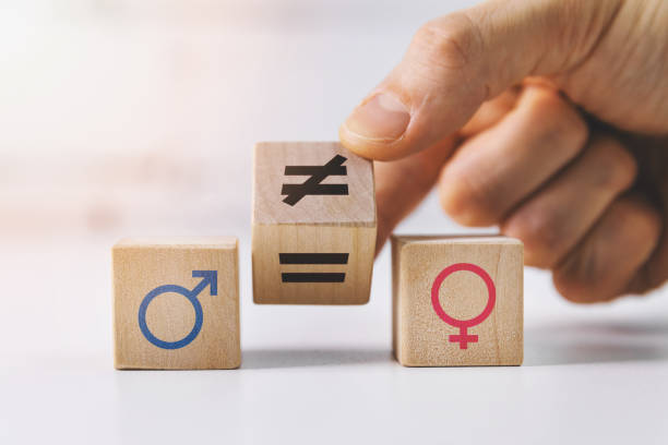 gender equality and discrimination concept - hand putting wooden blocks with symbols stock photo