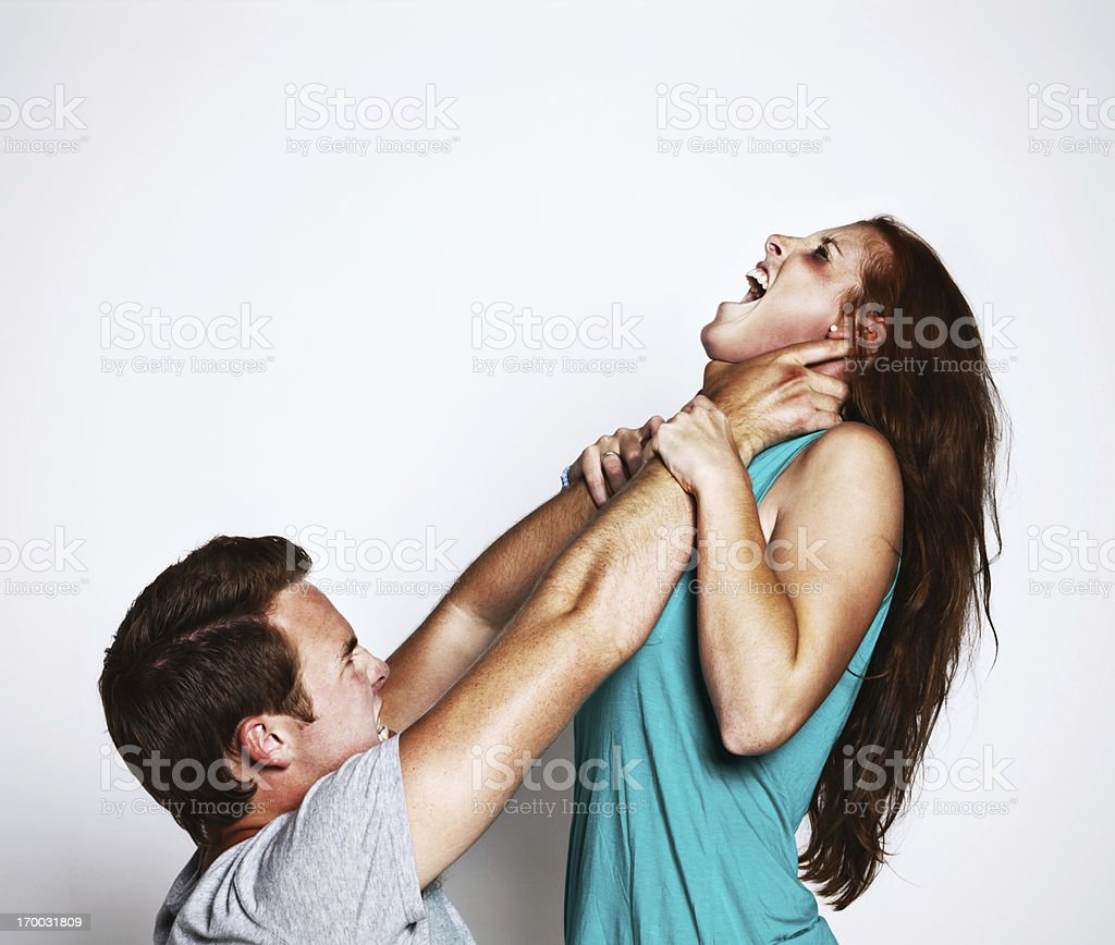 Gender violence: snarling young man throttles desperate struggling girl stock photo