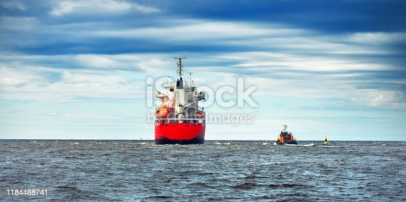 General cargo ship next to a tugboat in a open sea. Klaipeda, Lithuania