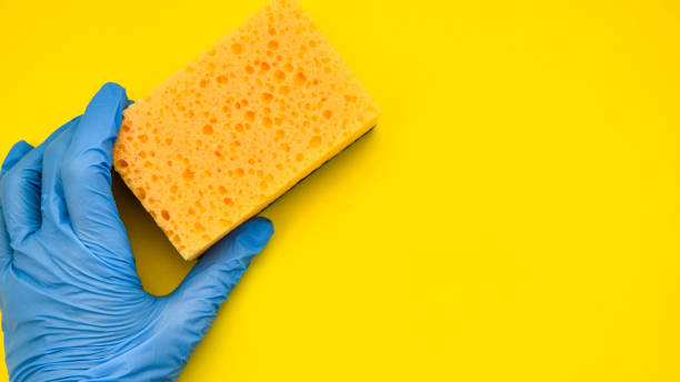 General cleaning, hand in rubber with sponge on yellow background, Copy space stock photo
