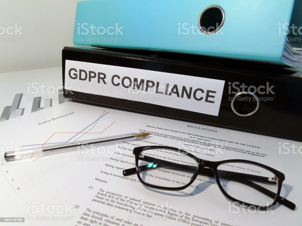 General Data Protection Regulation (GDPR) Compliance Lever Arch Folders on Desk with Documents (Legislative Text and Graphs), Glasses and Pen stock photo