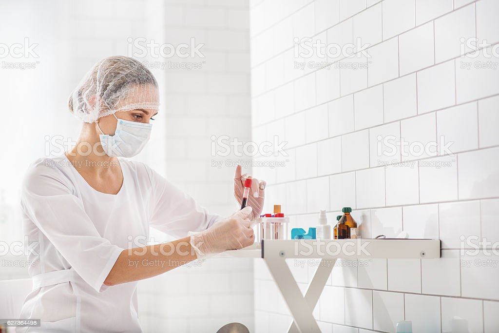 General practitioner examining tube with red liquid stock photo