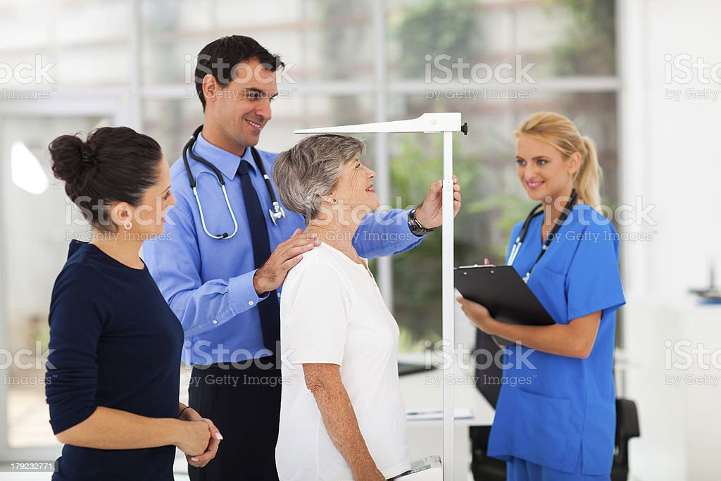 general practitioner measuring senior patient's height stock photo