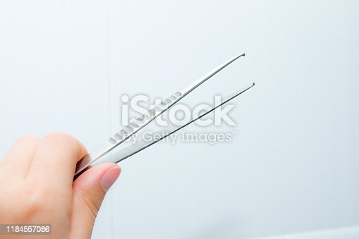 General purpose anatomical tweezers. Medical tweezers in hands on a white background. For plucking eyebrows.