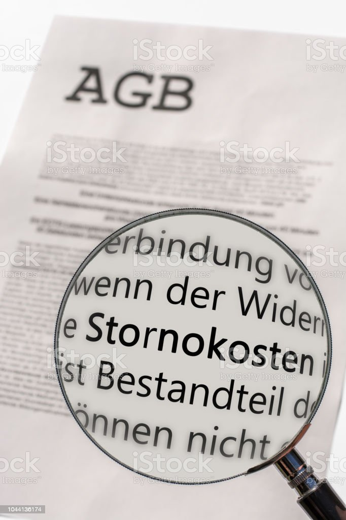 General terms and conditions are examined with the magnifying glass with the German word for cancellation costs stock photo