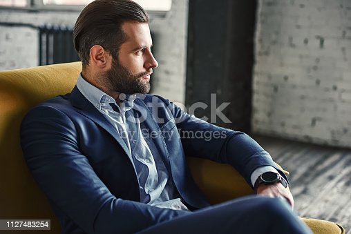 Generating ideas...Young and charming businessman is thinking about business while sitting on the sofa in his modern office