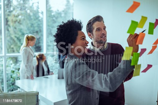 Coworkers using sticky notes on a glass wall during a meeting in the office