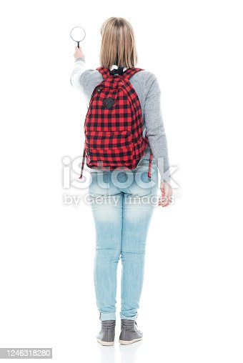 Rear view of aged 16-17 years old who is beautiful with blond hair generation z female detective standing in front of white background wearing sweater who is curious who is examining and holding magnifying glass and using headphones