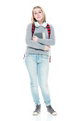 istock Generation z female high school student standing in front of white background wearing jeans and holding textbook and using headphones 1212391078