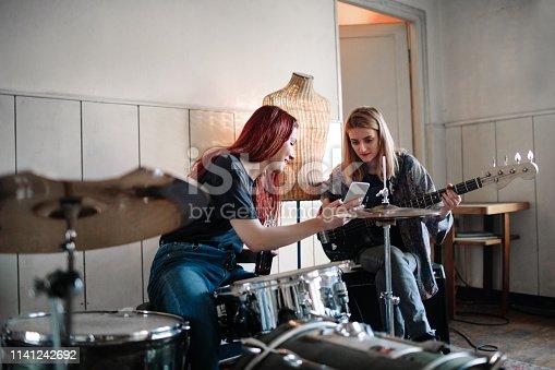 Generation Z Female Music Band On Rehearsal using smart phone.