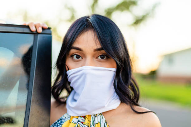 Generation Z Female Next to Automobile with Scarf as Face Mask Covering stock photo
