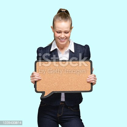 Waist up of who is beautiful with brown hair generation z female standing in front of colored background wearing jacket who is asking who is showing with hand and holding speech bubble with copy space