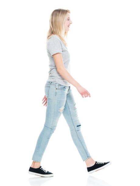 Generation z female walking in front of white background wearing t-shirt stock photo