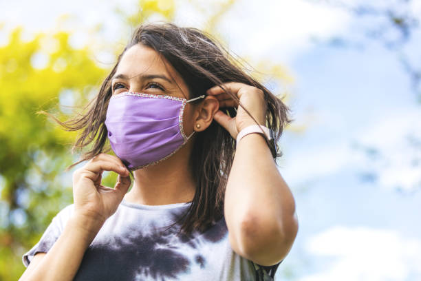 generation z female wearing face mask and social distancing - new normal foto e immagini stock