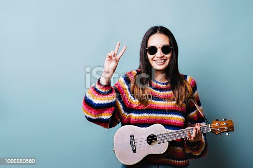 istock Generation Z Female with Ukulele and Peace Sign 1066680580