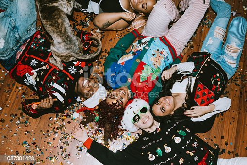 A group of young adult friends gather at a home for Christmas celebration over the holiday, dressed to fit the occasion with various Christmas accessories and ugly sweaters.  They relax on the floor, covered with confetti.