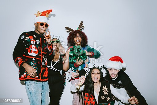 A group of young adult friends gather at a home for Christmas celebration over the holiday, dressed to fit the occasion with various Christmas accessories and ugly sweaters.  They pose for some photos, direct camera flash.