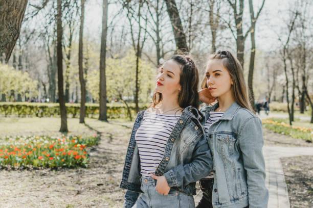 ジェネレーションz、ゲンz、ホームランド、祖国世代、ズーム、新しいサイレントジェネレーション。夏の公園で楽しんで二人の若い幸せな女の子の友人 - gen z ストックフォトと画像